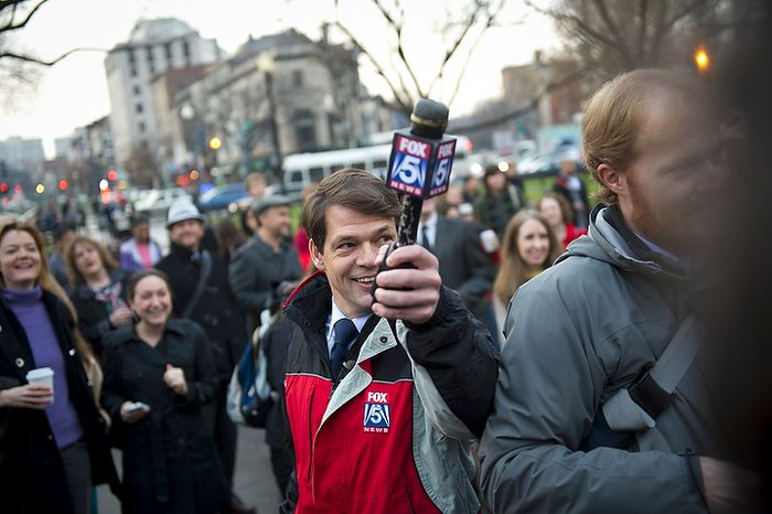 Fox 5 meteorologist Tucker Barnes holds up his microphone to get the groundhog's prediction during the inaugural Groundhog Day event at Dupont Circle in Washington on Thursday, Feb. 2, 2012. (Rod Lamkey Jr./The Washington Times)