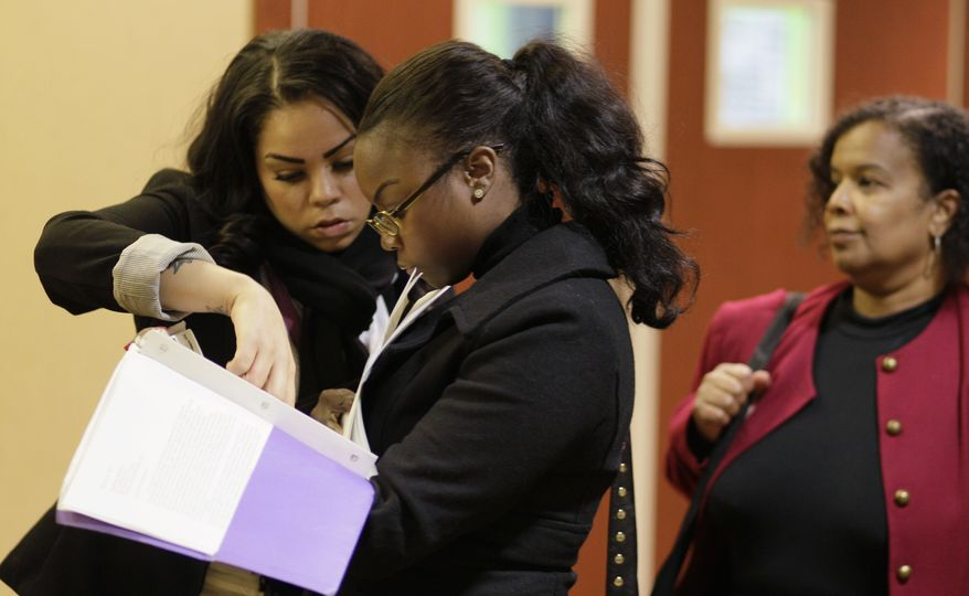 Job seekers Cameo Taylor (left) and Angelique McGuire (center), both of San Francisco, wait in line to register at a career fair event in San Francisco on Saturday, Jan. 28, 2012. (AP Photo/Eric Risberg)