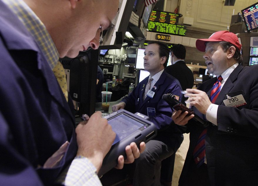 Trader Edward Schreier (right) works Feb. 3, 2012, with specialist John Alatzas (center) on the floor of the New York Stock Exchange. (Associated Press)