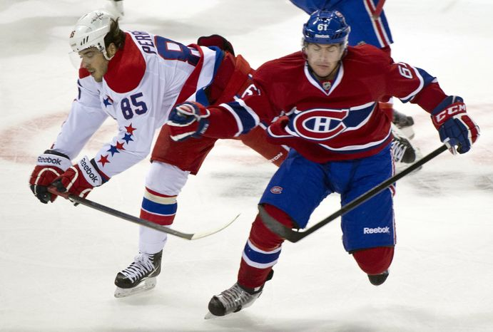 Washington Capitals' Mathieu Perreault , left, and Montreal Canadiens' Raphael Diaz collide during first period NHL hockey action, Saturday, Feb. 4, 2012 in Montreal. (AP Photo/The Canadian Press, Paul Chiasson)