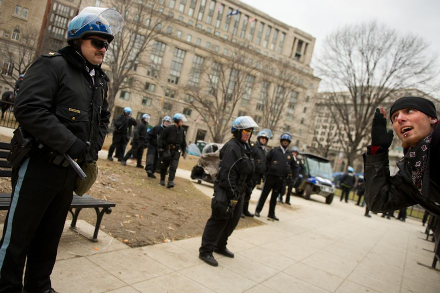 A protesters leans across a barrier to taunt a park police officer during a raid on the Occupy encampment at McPherson Square, Washington, D.C., Saturday, Feb. 4, 2012. Police and protesters clashed throughout the day as tents and camping equipment were removed by park police and maintenance officials, some dressed in hazmat suits.(Andrew Harnik/The Washington Times)