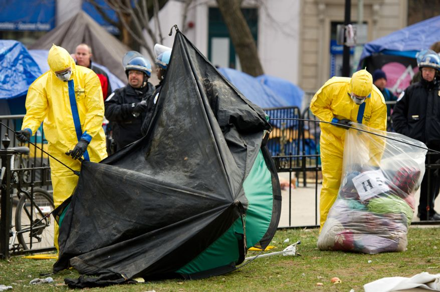 Park officials in hazmat suits break down tents and camping equipment during an early morning, peaceful raid on the Occupy encampment at McPherson Square, Washington, D.C., Saturday, Feb. 4, 2012. (Andrew Harnik/The Washington Times)