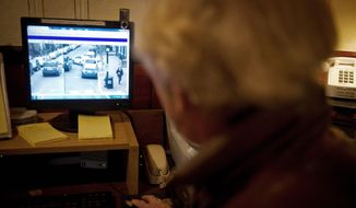 """Edward """"Chip"""" Dent shows a video surveillance image on a screen in the basement of his home on N Street NW in Georgetown. There is one functioning camera mounted high on the outside wall of Martin's Tavern at the corner of Wisconsin and N Streets NW that is aimed down N Street. (Rod Lamkey Jr./The Washington Times)"""