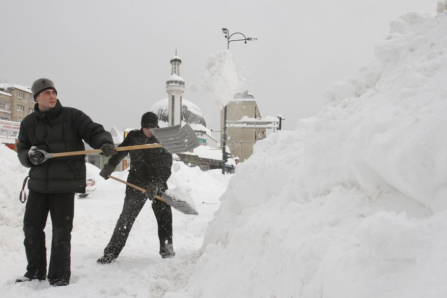 Bosnians shovel deep snow to clear a path for pedestrians in Sarajevo, Bosnia-Herzegovina, on Saturday, Feb. 4, 2012. Eastern Europe's unrelenting and deadly cold snap produced another heavy snowfall in the Balkans, trapping people in their homes and cars; causing power outages; and closing airports, railway stations and bus services. (AP Photo/Amel Emric)