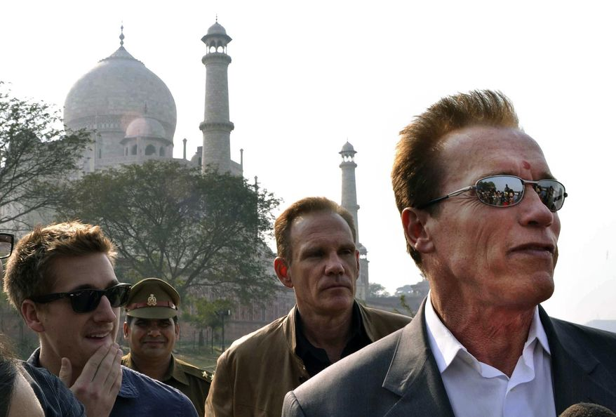 Austrian born Hollywood star and former Governor of California Arnold Schwarzenegger, right, stands in front of the historic Taj Mahal, in Agra, India, Friday, Feb. 3, 2012. Schwarzenegger, who is in the country attending a conference, was unable to visit the inside of the compound of the world famous site as it is closed Fridays. (AP Photo/Pawan Sharma)