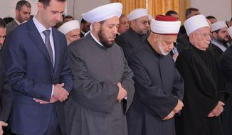 **FILE** Syrian President Bashar Assad (left) prays next to Syrian Grand Mufti Ahmad Hassoun (second from left) at the Al-Rawda Mosque in Damascus, Syria, on Sunday, Feb. 5, 2012, during a ceremony marking the birth of Islam's Prophet Mohammad. (AP Photo/SANA)