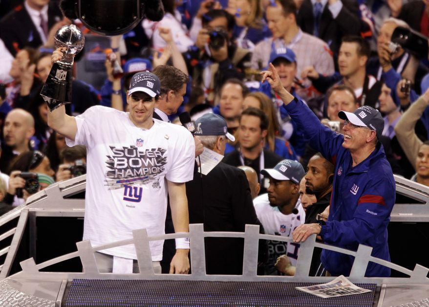 New York Giants quarterback Eli Manning and coach Tom Coughlin celebrate their 21-17 Super Bowl XLVI victory over the New England Patriots on Sunday, Feb. 5, 2012, in Indianapolis. (AP Photo/Charlie Riedel)