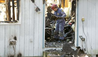 A fire investigator works his way through charred rubble on at the home where Josh Powell and his two sons were killed Sunday, in Graham, Wash., in what police said appeared to be a deliberately set fire. (Associated Press)