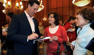 Former Sen. Rick Santorum of Pennsylvania signs an autograph after a health care speech Monday in Rochester, Minn. The Republican presidential hopeful is hoping to get back in the win column Tuesday with victories in caucuses in Minnesota and Colorado and in a nonbinding primary in Misssouri. (Associated Press)