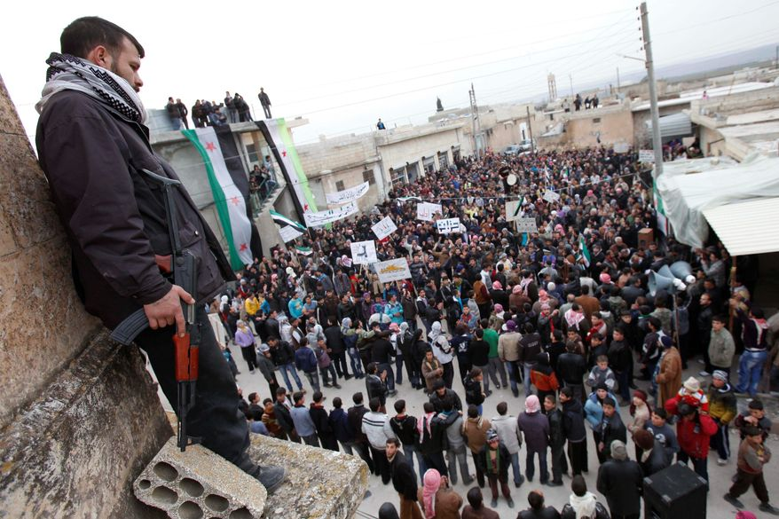 A member of the Free Syrian Army stands guard Monday during a rally of anti-regime demonstrators in Idlib, Syria. The U.S. closed its embassy in Syria, and Britain recalled its ambassador to Damascus in an escalation of Western pressure on President Bashar Assad to give up power. (Associated Press)