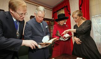 Actress Gillian Anderson (right) shows first editions of a Charles Dickens book to Britain's Prince Charles, his wife Camilla, Duchess of Cornwall, and David Wootton (left), the lord mayor of London, during a tour of the Dickens Museum in London on Tuesday. (Associated Press)