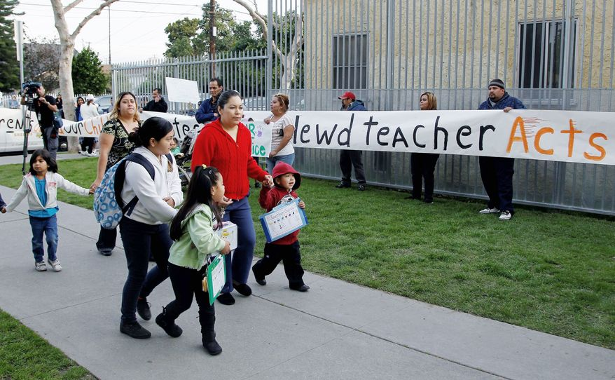 Parents bring their children to school as others protest outside Miramonte Elementary School in Los Angeles on Monday, Feb. 6, 2012. About three dozen parents and supporters staged a protest at the school, which has been rocked by abuse allegations. (Associated Press)
