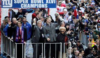 New York Giants quarterback Eli Manning hoists the Vince Lombardi trophy during a rally for the Super Bowl champions in East Rutherford, N.J. (Associated Press)