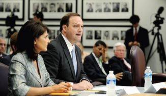 """** FILE ** South Carolina Attorney General Alan Wilson, here with Gov. Nikki Haley in June, argues in a lawsuit filed in February that the U.S. Justice Department erred in blocking the state from requiring voters to show government-issued photo identification to vote. The requirement """"will not disenfranchise any potential South Carolina voter,"""" he said. (Jeremy Lock/Special to The Washington Times)"""