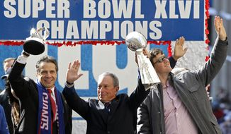 New York Gov. Andrew Cuomo (left) holds the Halas trophy, while New York Mayor Michael Bloomberg (center) holds the Vince Lombardi trophy as New York Giants quarterback Eli Manning waves to the crowd during a ticker-tape parade Feb. 7, 2012, celebrating the Giants' Super Bowl victory over the New England Patriots two days earlier. (Associated Press)