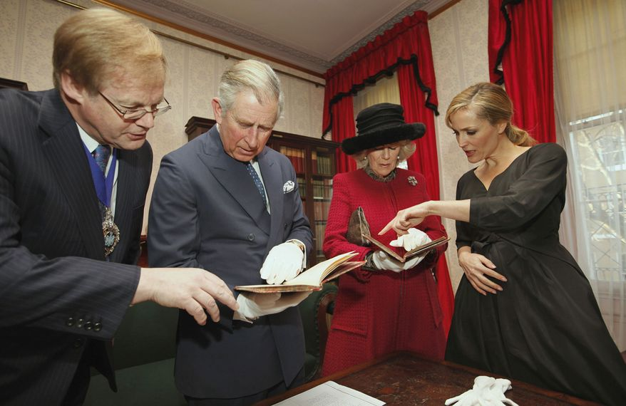 Actress Gillian Anderson (right) shows two first editions of a Charles Dickens book, with the author's annotations, to Britain's Prince Charles (second from left); his wife, Camilla, Duchess of Cornwall; and David Wootton, lord mayor of London, during a tour of the Dickens Museum in London on Tuesday, Feb. 7, 2012, the 200th anniversary of Dickens' birth. (AP Photo/Andrew Winning, Pool)
