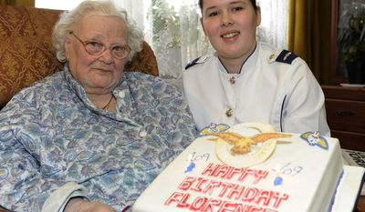 Florence Green (left) receives a birthday cake from LAC Hannah Shaw on behalf of the Royal Air Force at Mrs. Green's home in King's Lynn, England, on Feb. 19, 2011, Mrs. Green's 110th birthday anniversary. (AP Photo/Sac Chris Hill/U.K. Ministry of Defense)