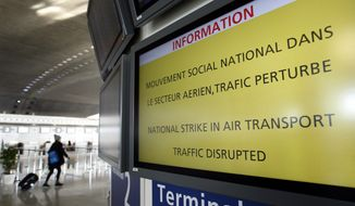 A traveler walks Feb. 7, 2012, next to an information board at Paris Charles de Gaulle airport in Roissy-en-France. (Associated Press)