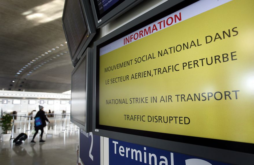 A traveler walks Feb. 7, 2012, next to an information board at Paris Charles de Gaulle airport in Roissy-en-France. (Associated Press)