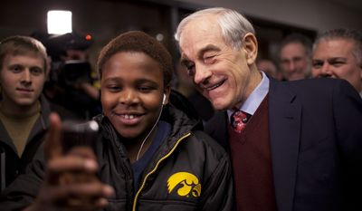 Texas Rep. Ron Paul, who is running for the GOP presidential nomination, poses Feb. 7, 2012, for a photo with a youth as voters attend their caucus at Coon Rapids Middle School in Coon Rapids, Minn. (Associated Press/The Star Tribune)