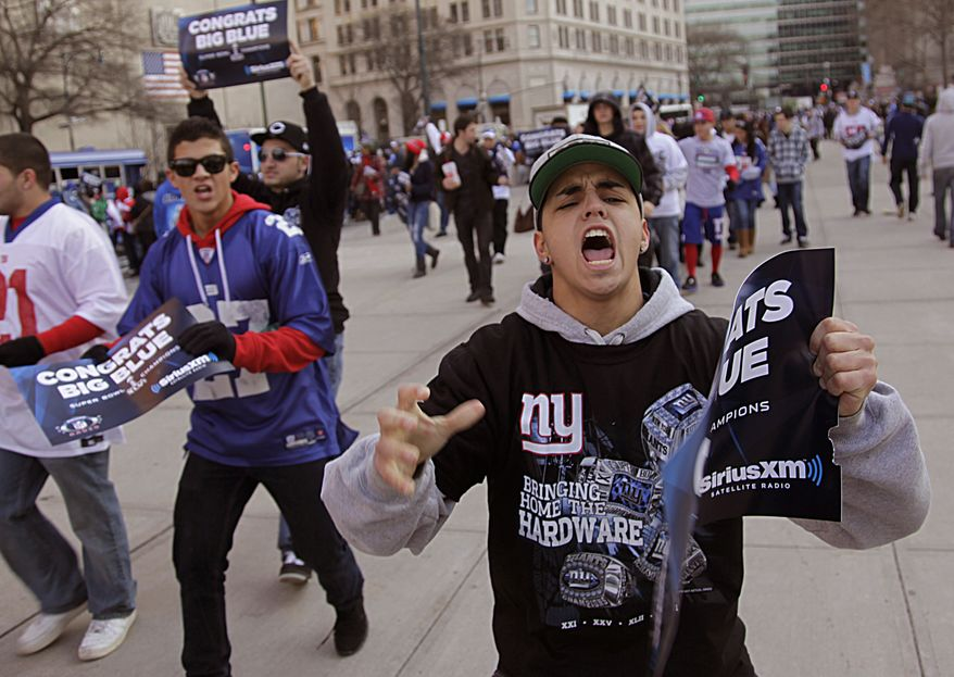 Fans cheer Feb. 7, 2012, as they arrive in lower Manhattan for the start of the New York Giants Super Bowl parade in New York. (Associated Press)