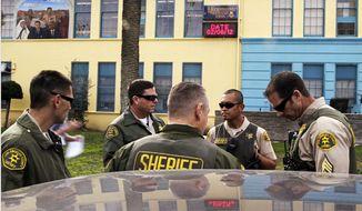 ** FILE ** Los Angeles County sheriff's deputies stand outside Miramonte Elementary School in Los Angeles on Feb. 6, 2012. (Associated Press)
