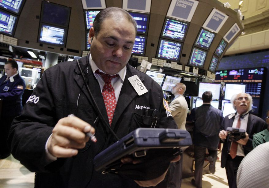 ** FILE ** Trader Anthony Riccio (left) works on the floor of the New York Stock Exchange on Friday, Feb. 3, 2012. (AP Photo/Richard Drew)