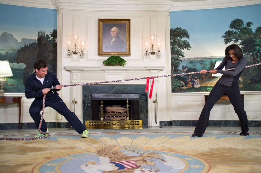 """First lady Michelle Obama and comedian Jimmy Fallon compete at tug-of-war at the White House during a taping of Mr. Fallon's """"Late Night"""" program Jan. 25. Mrs. Obama has made the talk-show rounds while promoting her """"Let's Move!"""" fitness campaign. (The White House via Associated Press)"""