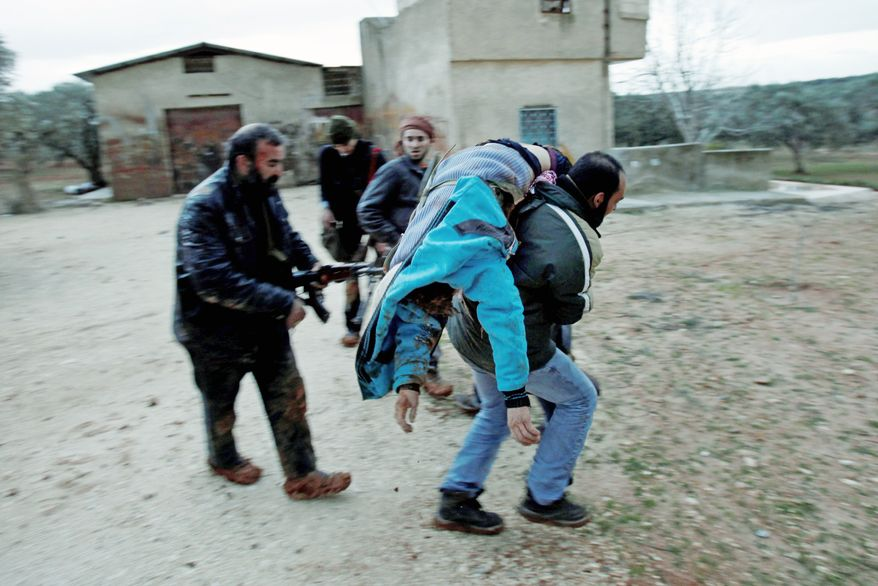 A Syrian rebel evacuates an injured fellow rebel during an exchange of fire with army troops in Idlib, Syria, on Wednesday. The European Union will impose harsher sanctions on Syria, a senior EU official said, as Russia tried to broker talks to end the violence. (Associated Press)