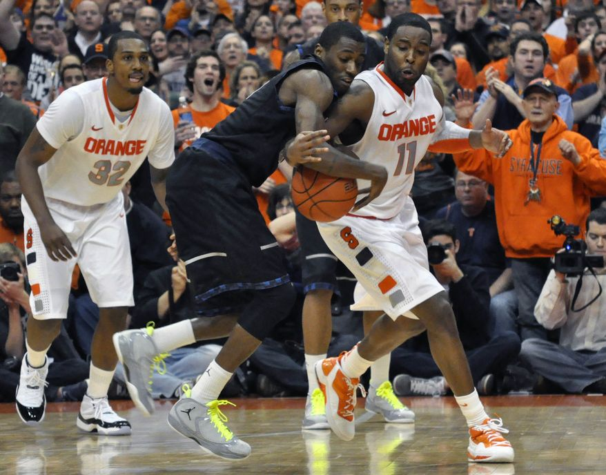 Syracuse's Scoop Jardine, right, knocks the ball loose from Georgetown's Jason Clark, forcing a turnover to end the game in overtime, in an NCAA basketball game in Syracuse, N.Y., Wednesday, Feb. 8, 2012. Syracuse won 64-61. (AP Photo/Kevin Rivoli)