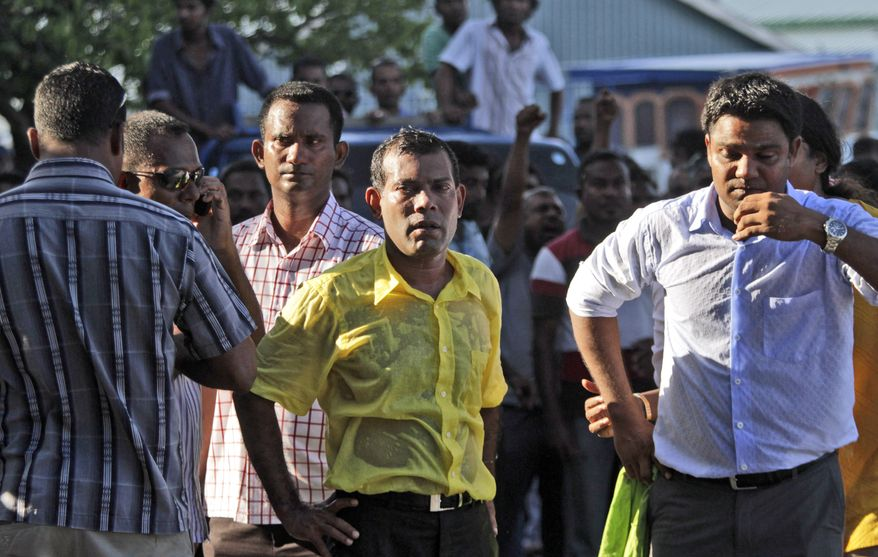 Mohamed Nasheed (center), who resigned Tuesday as president of Maldives, stands with his supporters after police fired tear gas at them during a rally in Male, Maldives, on Wednesday, Feb. 8, 2012. (AP Photo/Eranga Jayawardena)