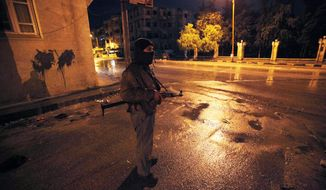 A Syrian rebel stands guard Feb. 8, 2012, at a street in Idlib, Syria. (Associated Press)