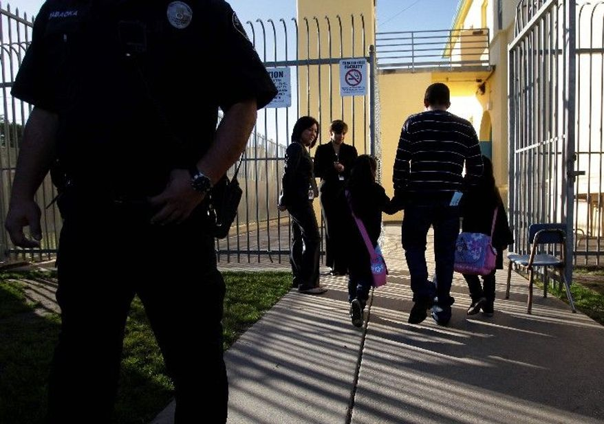 An adult accompanies two students into Miramonte Elementary School in Los Angeles on Thursday. Children come back to the elementary school where the entire staff has been replaced after the arrests of two former teachers on charges of committing lewd acts with students in class. (Associated Press)