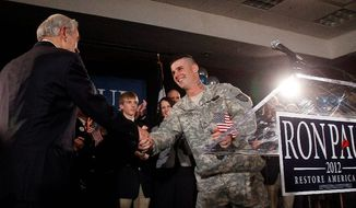 Presidential candidate Rep. Ron Paul, Texas Republican, shakes hands with Army Cpl. Jesse Thorsen during his January caucus night rally, in Ankeny, Iowa. Mr. Paul has been getting extensive campaign-contribution support from enlisted people and civilians in the military, far exceeding his GOP rivals for the nomination. (Associated Press)