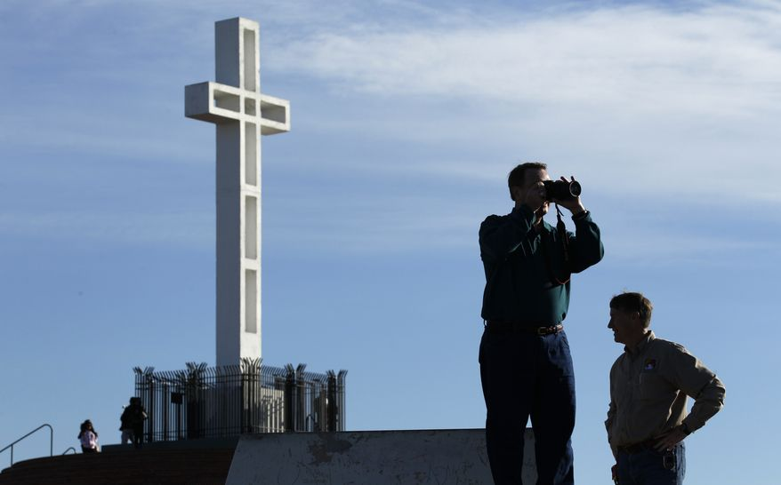 ** FILE ** The Rev. John Fredericksen (left) of Orlando, Fla., with Burdette Streeter of San Diego, takes a picture in front of the war memorial cross on Mount Soledad in San Diego in January 2011. (AP Photo/Gregory Bull)