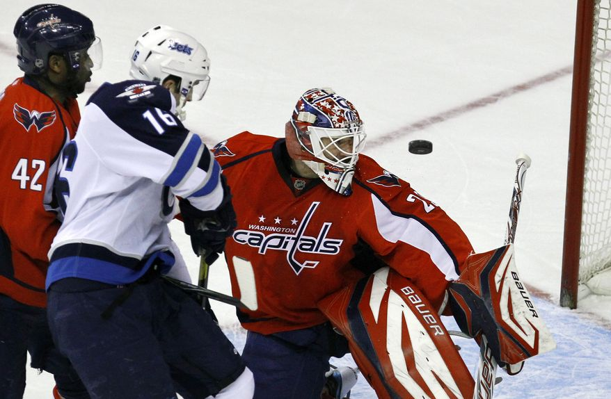 Washington Capitals goalie Tomas Vokoun (29) watches the puck on an unsuccessful shot in front of Capitals right wing Joel Ward (42) and Winnipeg Jets left wing Andrew Ladd (16) during the first period of an NHL hockey game in Washington, on Thursday, Feb. 9, 2012. (AP Photo/Jacquelyn Martin)