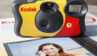 A Kodak FunSaver single-use camera sits on a box of Kodak inkjet paper. (AP Photo/Mark Lennihan)