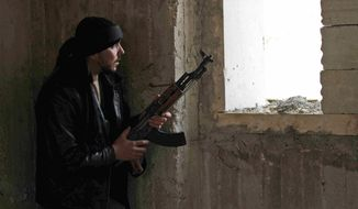 A Syrian rebel peers through a window in Idlib, Syria, on Thursday, Feb. 9, 2012. (AP Photo)