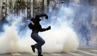 A protester throws a stone toward riot police during clashes in Athens, Friday, Feb. 10, 2012. Thousands took to the streets of Athens as unions launched a two-day general strike against planned austerity measures on Friday, a day after Greece's crucial international bailout was put in limbo by its partners in the 17-nation eurozone. (AP Photo/Petros Giannakouris)