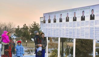 Residents look Feb. 7, 2012, at a presidential election poster depicting the candidates in Ashgabat, Turkmenistan. (Associated Press)