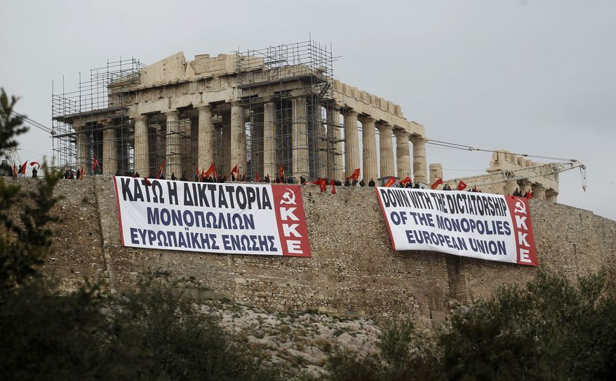 Greek communist party members wave party's flags after hanging banners in Greek and English denouncing EU policies under the temple of Parthenon at the Athen's Acropolis hill on Saturday, Feb. 11, 2012. (AP Photo/Petros Giannakouris)
