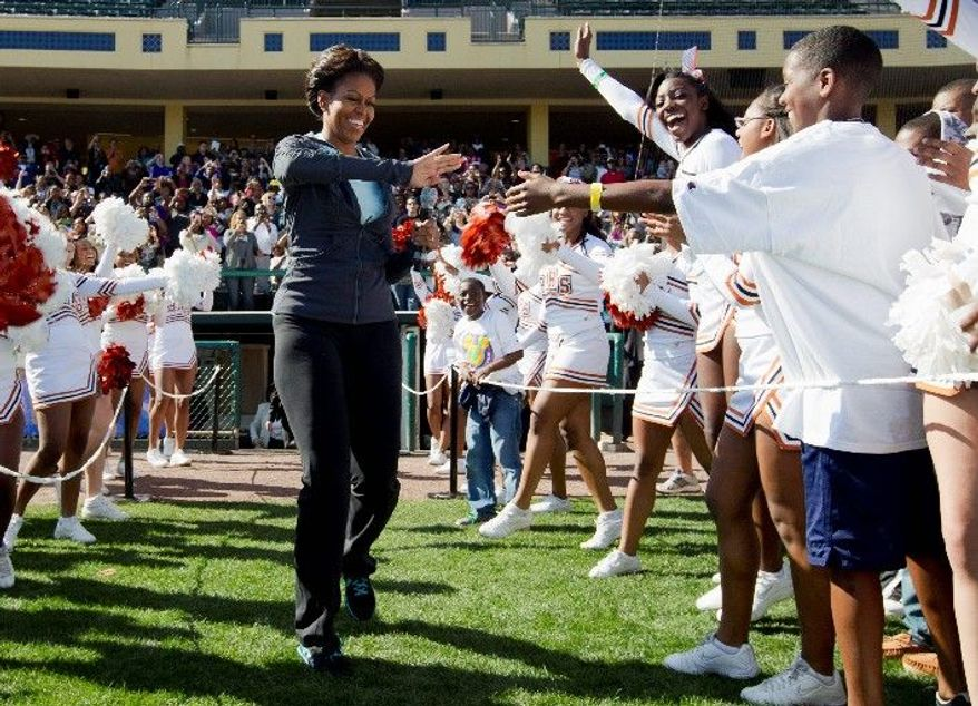"""First lady Michelle Obama greets children as she arrives at the ESPN Wide World of Sports Complex at the Walt Disney World Resort on Saturday in Orlando, Fla., in her three-day tour marking the second anniversary of the """"Let's Move"""" exercise initiative. (Associated Press)"""