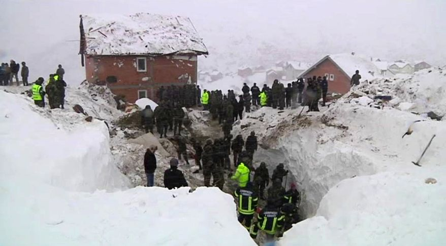 Rescuers clear snow and rubble from a house flattened by an avalanche in Restelica, Kosovo, on Sunday, Feb. 12, 2012. (Associated Press Television News)