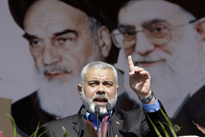 **FILE** Ismail Haniyeh, the Hamas prime minister of the Gaza Strip, delivers a speech in front of portraits of the late Iranian revolutionary founder, Ayatollah Ruhollah Khomeini (left), and Supreme Leader Ayatollah Ali Khamenei during a visit to Tehran on Feb. 11, 2012. (Associated Press)