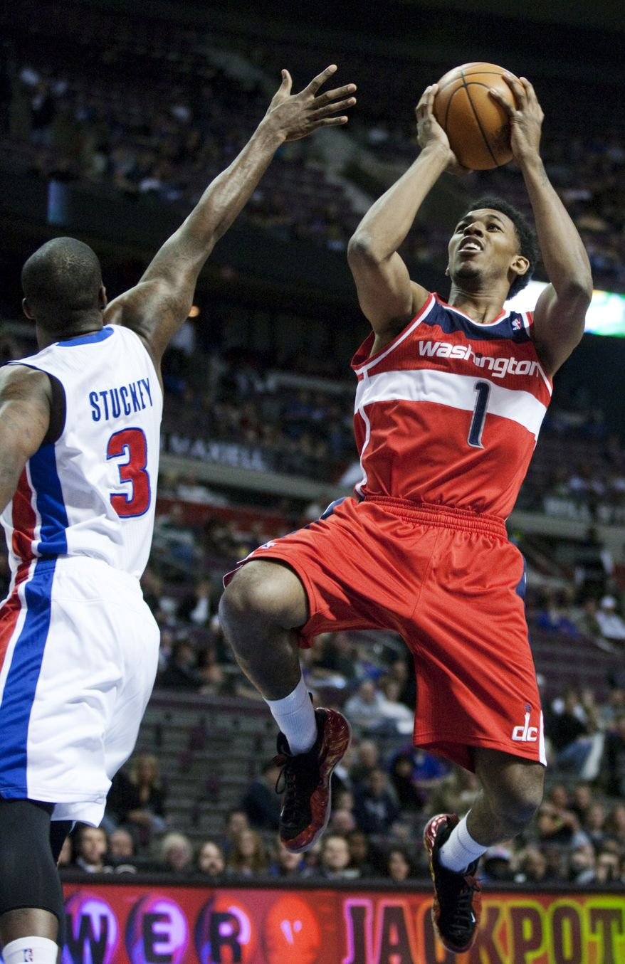 Washington Wizards' Nick Young (1) shoots against Detroit Pistons' Rodney Stuckey (3) in the first half of an NBA game, Sunday, Feb. 12, 2012, in Auburn Hills, Mich. The Wizards won 98-77. (AP Photo/Duane Burleson)