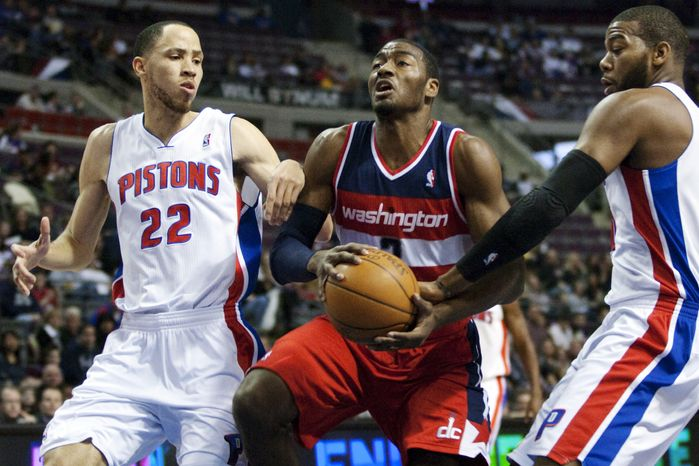 Washington Wizards' John Wall, center, drives between Detroit Pistons' Tayshaun Prince (22) and Greg Monroe, right, in the first half of an NBA game, Sunday, Feb. 12, 2012, in Auburn Hills, Mich. (AP Photo/Duane Burleson)