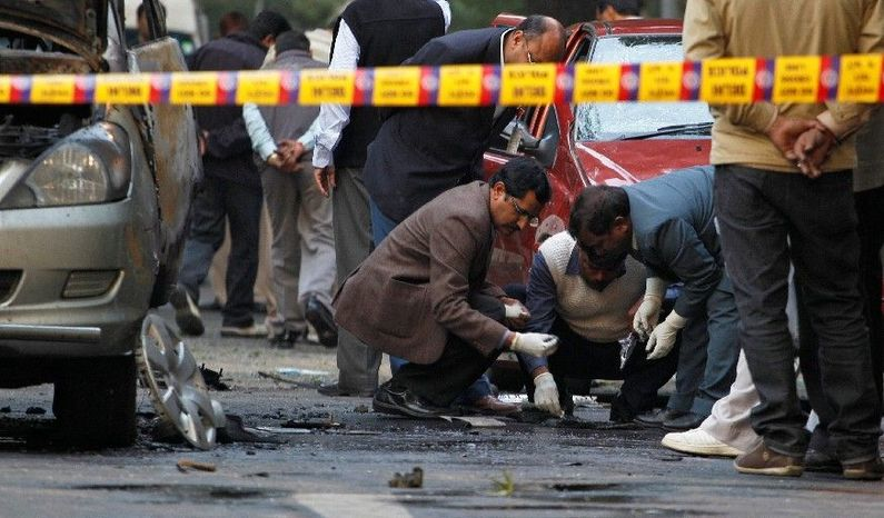 Indian security and forensic officials examine the spot where a bomb blew up an Israeli Embassy car. The attack was similar to ones on Iranian nuclear scientists. (Associated Press)
