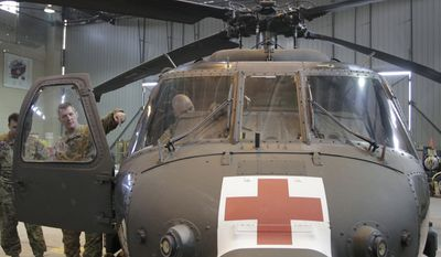 Army Maj. Graham Bundy (center left), a medevac commander from Sussex, Wis., points to the inside of a U.S. medevac helicopter in a hangar at Bagram Air Field, north of Kabul, Afghanistan, on Saturday, Jan. 28, 2012. (AP Photo/Musadeq Sadeq)