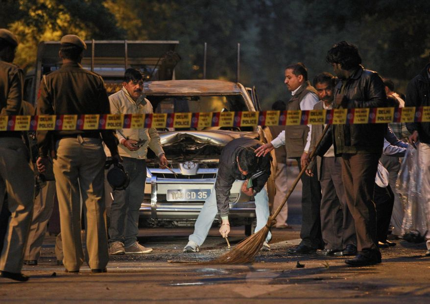 Indian police forensics experts collect evidence on Feb. 13, 2012, after an explosion tore through a car belonging to the Israel Embassy in New Delhi. Assailants targeted Israeli diplomats in India and Georgia in near-simultaneous strikes Monday that Israeli Prime Minister Benjamin Netanyahu blamed on archenemy Iran, and its Lebanese proxy, Hezbollah. (Associated Press)
