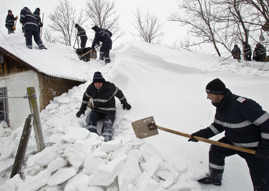 Firefighters dig 77-year-old Elisabeta Dumitrache's house out of the snow Feb. 11, 2012, in the village of Carligul Mic, Romania. (Associated Press)